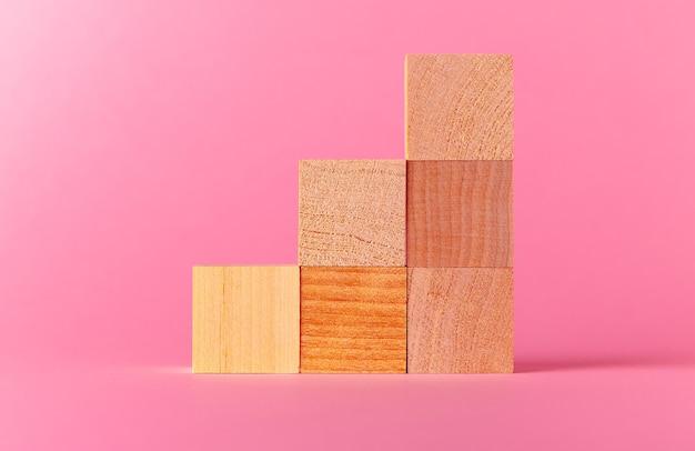 Cubos de madeira de brinquedo com espaço de cópia contra um fundo rosa