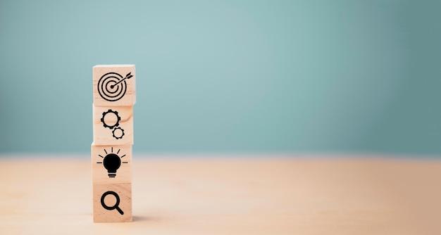 Cubos de madeira empilhamento de placa de alvo com seta no ícone de outros, definindo o conceito de alvo objetivo de negócios.