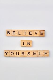 Cubos de madeira estão fazendo citações inspiradoras. conceito de acreditar em si mesmo sobre fundo branco.