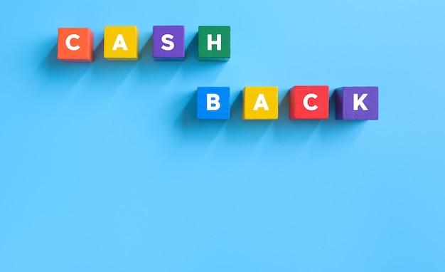 Cubos de madeira multicoloridos com a palavra cash back sobre fundo azul. dinheiro, conceito de negócio de impostos.