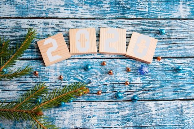 Cubos de madeira para as datas do ano novo vista superior conceito de ano novo azul fundo de madeira ramo de abeto