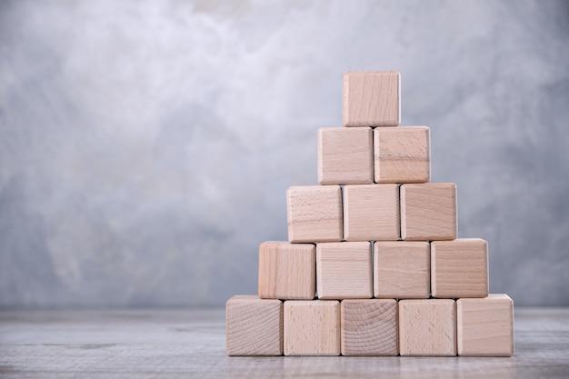 Cubos de madeira são empilhados em forma de escadas em uma mesa de madeira. o conceito de desenvolvimento, crescimento, o chefe, o melhor.