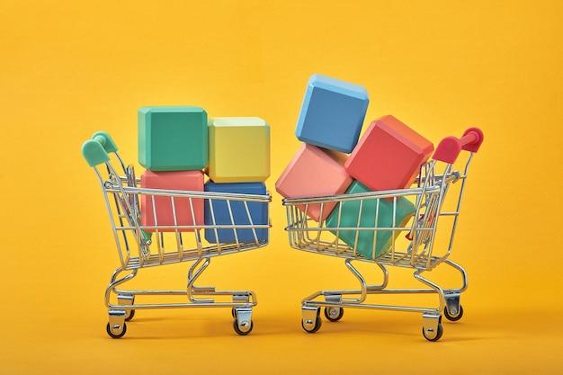 Cubos de madeira vazios copiam espaço com carrinhos de compras em fundo amarelo