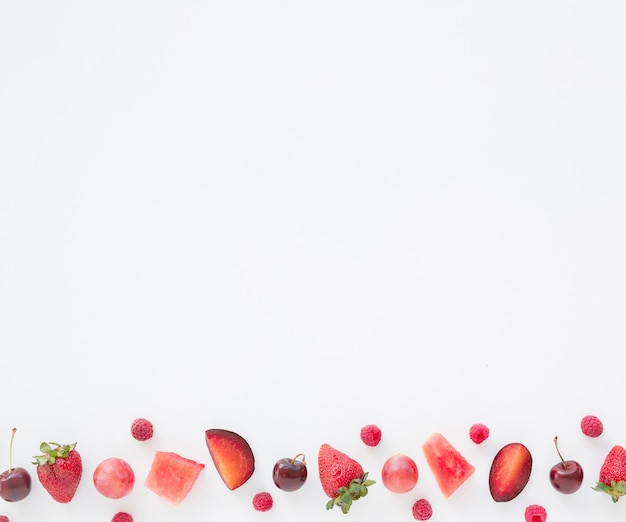 Cubos de melancia; framboesas; ameixa; cerejas e morangos ao lado de fundo branco
