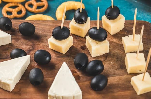 Cubos de queijo e azeitonas pretas em uma placa de madeira com biscoitos