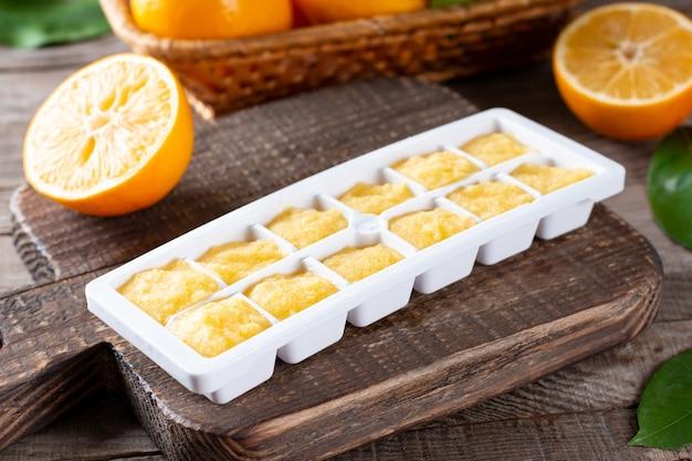 Cubos de suco de limão congelados na bandeja sobre uma mesa de madeira, closeup