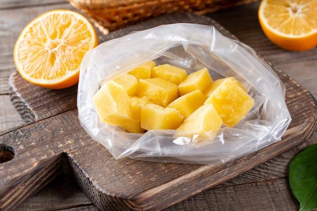 Cubos de suco de limão congelados no saco sobre uma mesa de madeira, frutas congeladas
