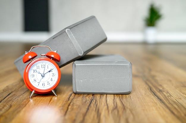 Cubos de suporte cinza para esportes com despertador vermelho no piso de madeira