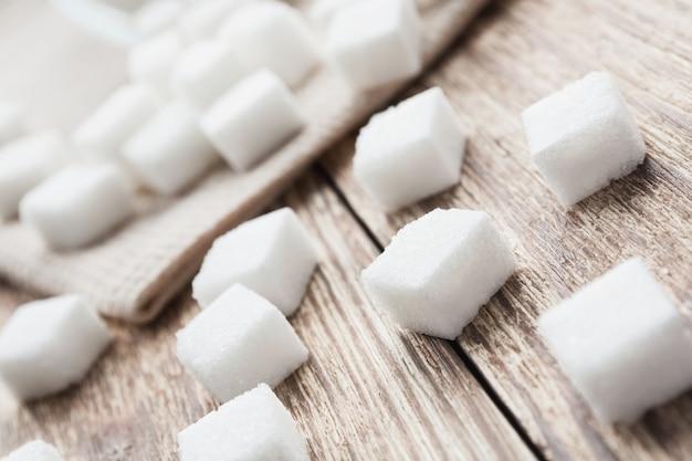 Cubos do açúcar branco na superfície de madeira e na toalha bege.
