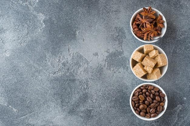 Cubos do açúcar mascavado, feijões de café e anis de estrela no concreto. espaço da cópia