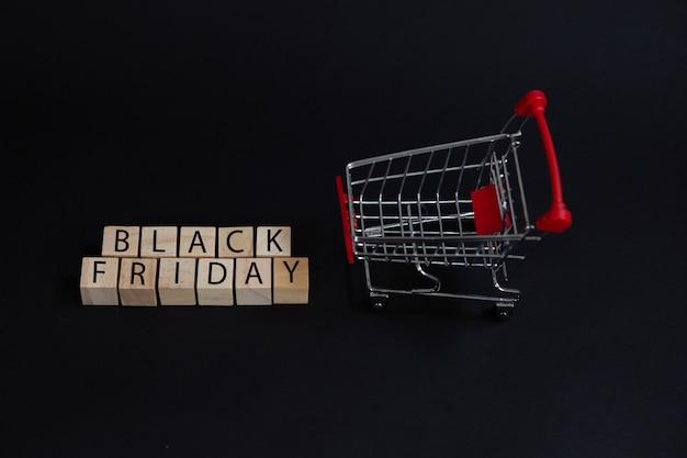 Cubos pretos de sexta-feira e um carrinho de supermercado como um conceito de vendas.