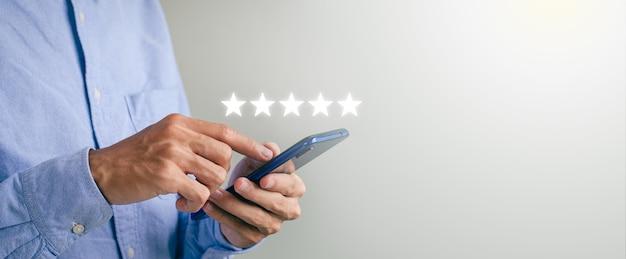 Cubra a mão do cara usando um smartphone e dê o símbolo de cinco estrelas para aumentar a avaliação do serviço ao cliente do conceito da empresa. experiências de atendimento ao cliente e pesquisas de satisfação