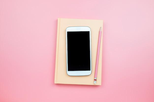 Cubra o lápis do telefone móvel do caderno no estilo pastel do fundo cor-de-rosa