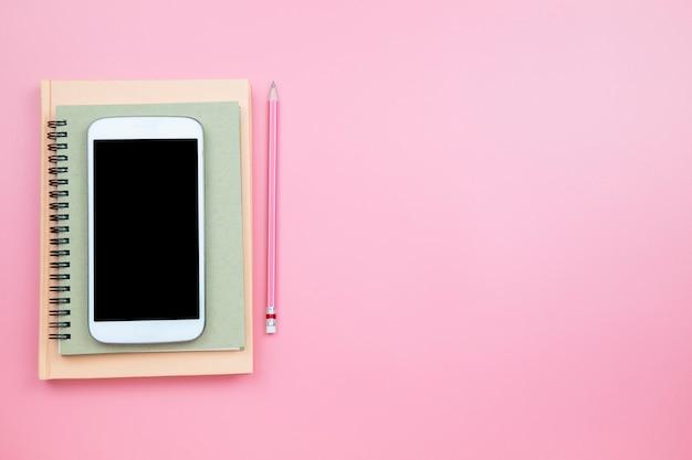 Cubra o lápis do telefone móvel do caderno no fundo cor-de-rosa
