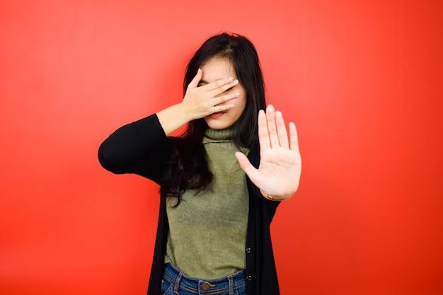 Cubra os olhos dela e faça sinal de rejeição de lindas mulheres asiáticas usando suéter preto isolado no vermelho