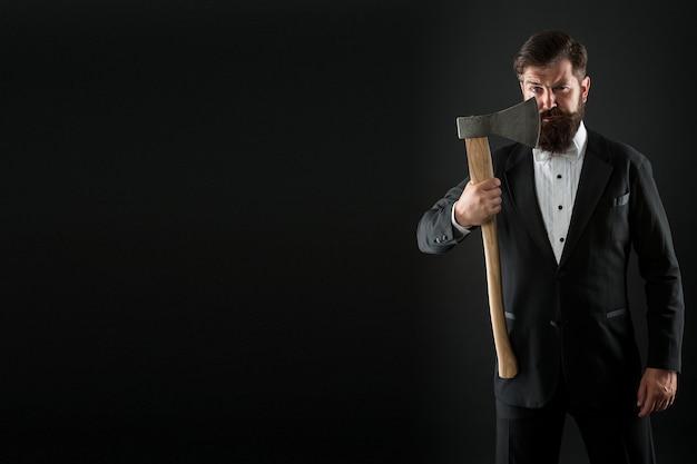 Cuidado além do cabelo. hipster mantém a lâmina afiada do machado no rosto com a barba por fazer. homem barbudo segurar machado. rotina de cuidados com a pele dos homens. cuidados com a pele barbada. cuidados com a pele. barbearia. cabeleireiro. adicionando cuidado ao seu cabelo, copie o espaço.