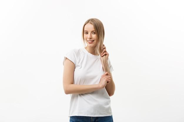 Cuidado capilar. jovem caucasiana penteando o cabelo com o dedo isolado no fundo branco