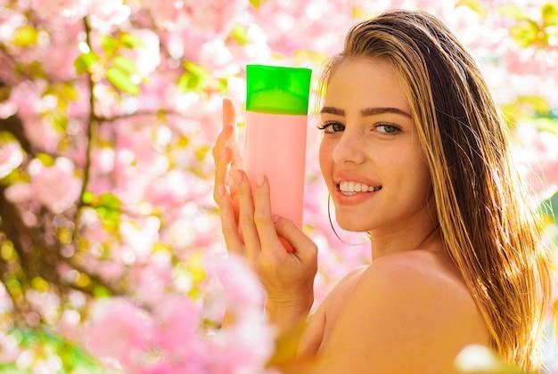 Cuidado capilar. menina sorridente com cosméticos para cabelo. shampoo ou bálsamo para o cabelo. cosméticos naturais à base de plantas.