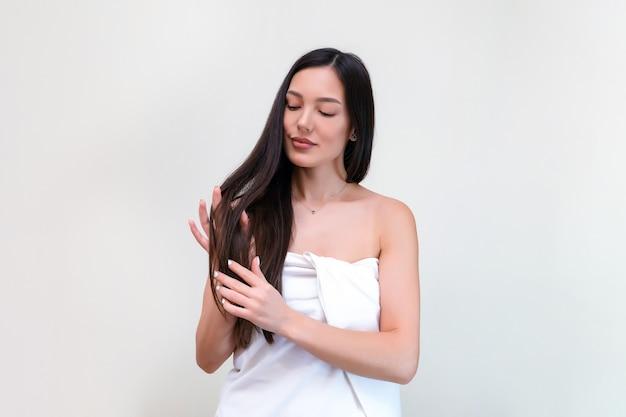 Cuidado capilar. mulher jovem e bonita em uma toalha toca seu cabelo com as mãos.