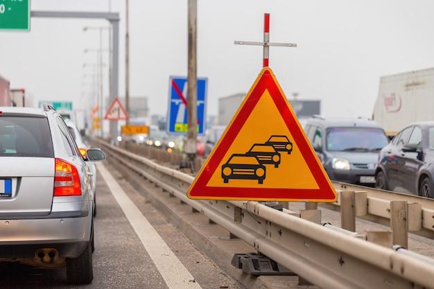 Cuidado com o sinal de trânsito de engarrafamento em uma rodovia com veículos presos esperando em ambos os lados.
