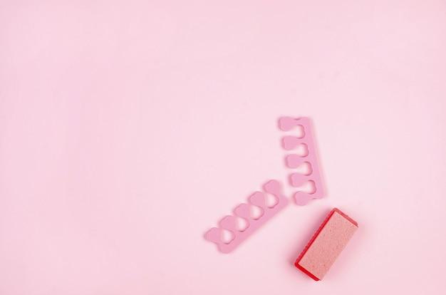 Cuidado com os pés. acessórios de pedicure conjunto de ferramentas em fundo rosa