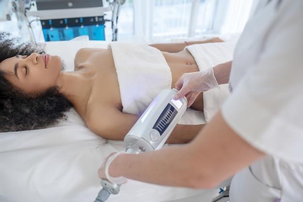 Cuidado corporal eficaz. mulher jovem com os olhos fechados deitada de costas durante um procedimento cosmético seguro e as mãos do médico