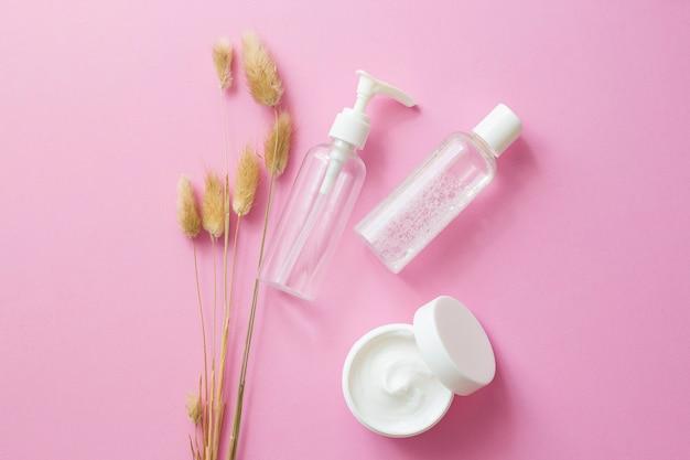 Cuidado, cosméticos orgânicos para o rosto. garrafas brancas e transparentes em um fundo rosa