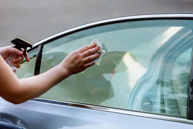 Cuidado de carro - mulher que lava um carro à mão usando o carro da limpeza de pano do microfiber.