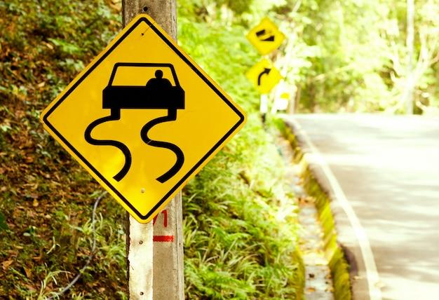 Cuidado de estradas escorregadias - sinais de trânsito ao lado da estrada do país
