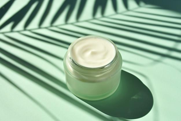 Cuidado de pele do verão, cosméticos naturais, frasco de creme cosmético aberto com silhueta em folha de palmeira.