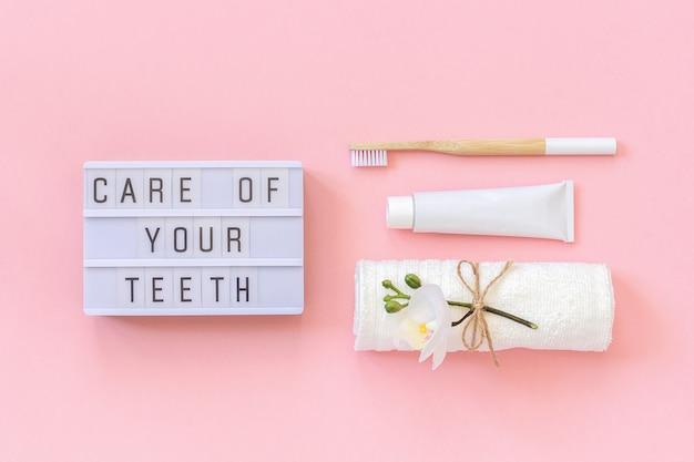 Cuidado de seus dentes texto na mesa de luz, escova de bambu natural eco-friendly para dentes, toalha, tubo de creme dental