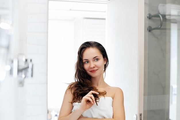 Cuidado do cabelo e do corpo. mulher tocando o cabelo e sorrindo enquanto se olha no espelho. retrato de menina feliz com o cabelo molhado no banheiro, aplicando condicionador e óleo. menina usa creme hidratante de proteção