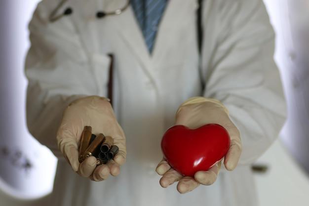Cuidado do coração e luva no conceito de mão do médico de ajuda