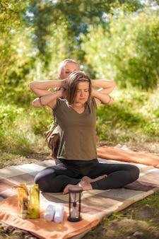 Cuidado do corpo. a massagem mestre aplica suas habilidades de massagem em seu cliente à luz do dia.