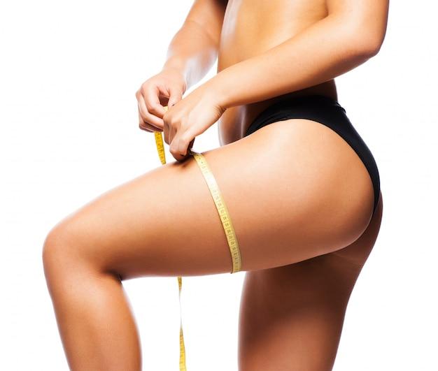 Cuidado do corpo da mulher e medida amarela nas coxas