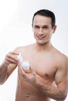 Cuidado do corpo. homem atraente, alegre e bem construído sorrindo e mostrando creme para o corpo enquanto cuida de sua pele