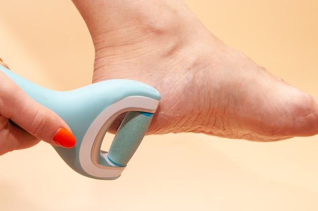 Cuidado e limpeza dos pés da mulher da pele áspera.