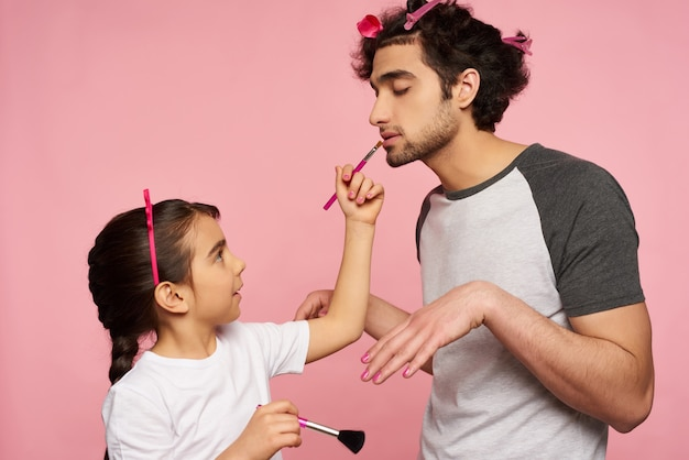 Cuidado família árabe. menina faz maquiagem para o pai.