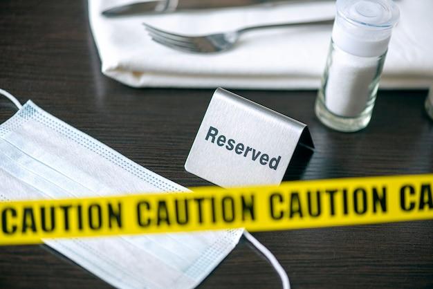 Cuidado - fita amarela sobre a mesa no café ou restaurante e o sinal reservado. distanciamento social