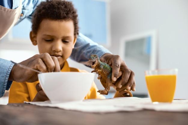 Cuidado paternal. pai amoroso e atencioso ajudando seu filho a alimentar um dinossauro de brinquedo com os cereais da tigela enquanto o menino toma o café da manhã