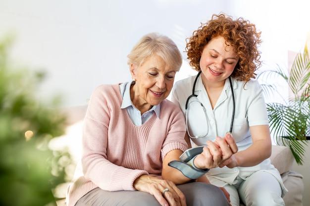 Cuidador amável que mede a pressão sanguínea de uma mulher idosa feliz na cama no lar de idosos.