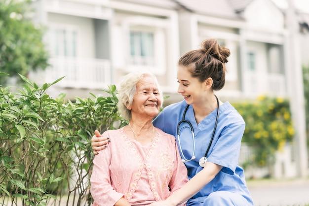 Cuidador com mulher idosa asiática ao ar livre