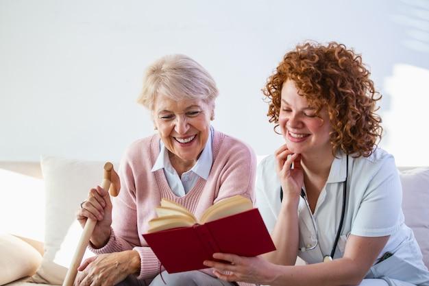 Cuidador de mulher que lê um livro ao sentar-se com a mulher sênior feliz no lar de idosos.