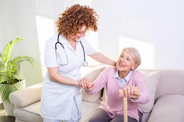Cuidador feminino, ajudando a mulher sênior se levantar do sofá na sala de estar. enfermeira de sorriso que ajuda à mulher superior a levantar-se.