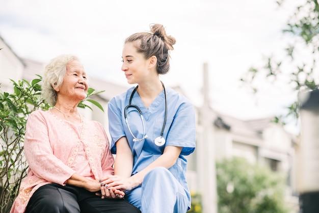 Cuidador, segurando a mão da mulher idosa feliz