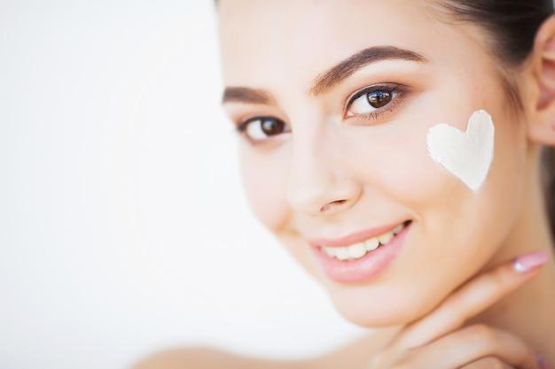 Cuidados com a pele. bela modelo aplicando creme de tratamento cosmético no rosto