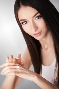Cuidados com a pele beleza. mulher bonita, aplicar creme facial