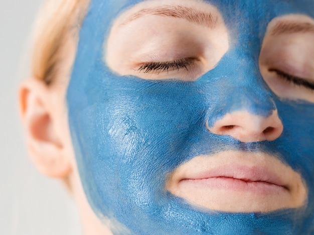 Cuidados com a pele. cara da mulher com fim azul da máscara da lama da argila acima. mulher cuidando da pele oleosa. tratamento de beleza.