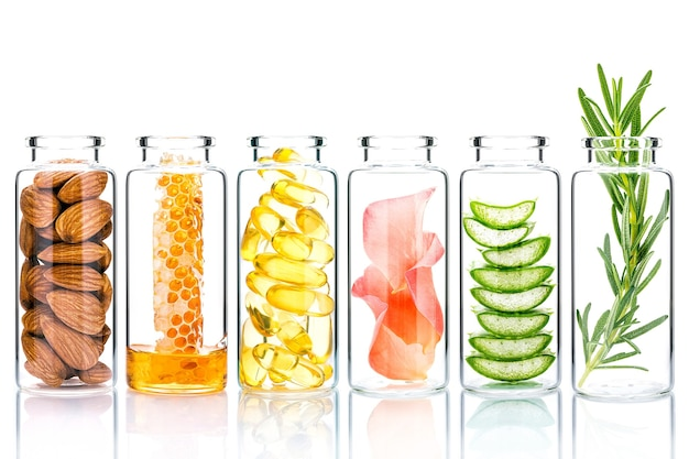 Cuidados com a pele caseiros com ingredientes naturais e ervas em frascos de vidro isolam em branco.