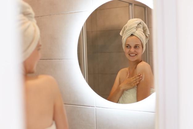 Cuidados com a pele, cosmetologia, procedimentos diários. o reflexo no espelho da mulher usa produtos para a pele em casa no banheiro claro, tendo expressão feliz, sendo embrulhado em toalha.